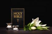 lilie, svíčky a svatá bible na černém pozadí, pohřební koncept