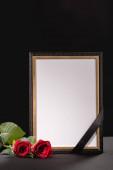 dvě červené růže a zrcadlo se stuhou na černém pozadí, pohřební koncept