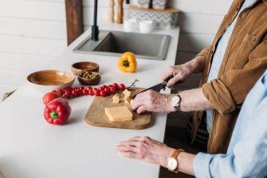 Kocasının yanında yaşlı bir kadının mutfak masasında peynir keserken görüntüsü bulanık arka planda.