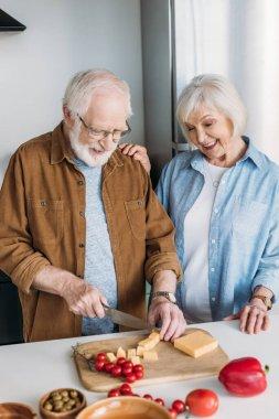 Kocasının yanında mutlu, yaşlı bir eş, mutfakta sebzelerin yanında peynir doğruyor.