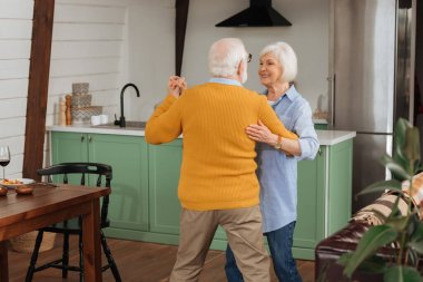 back view of elderly husband dancing with happy wife in kitchen