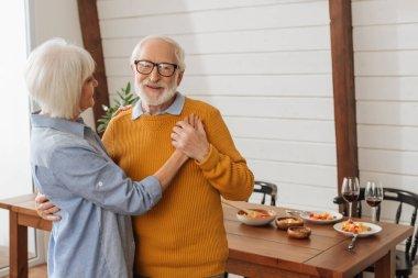 Mutfakta karısıyla dans ederken kameraya bakan yaşlı koca bulanık arka planda dans ediyor.