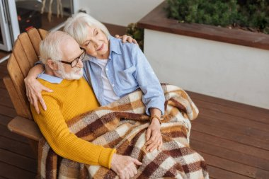 Smiling senior couple with plaid blanket, hugging and looking away while sitting in armchair on terrace on blurred background stock vector