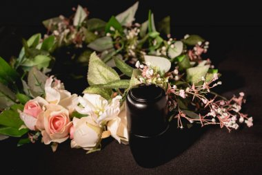 Rose bouquet and urn with ashes on black background, funeral concept stock vector