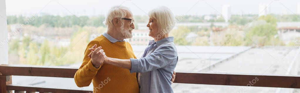 Happy senior couple looking at each other while dancing on terrace on blurred background, banner stock vector