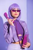 mladá žena oblečená v panenka styl s retro telefon na fialové barevné pozadí