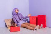 junge Frau im Puppenstil sitzend mit Einkaufstaschen auf violettem Hintergrund