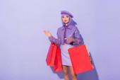mladá žena oblečená v panenka styl s červenými nákupními taškami na fialové barevné pozadí