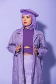 mladá žena oblečená v panenka styl v baretu pózování na fialové barevné pozadí