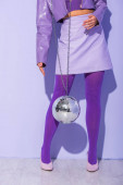 cropped view of young woman dressed in doll style with disco ball on violet colorful background