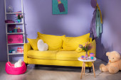Fotografie buntes Puppenwohnzimmer mit gelbem Sofa