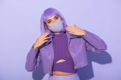 young woman dressed in doll style in medical mask with disco ball on violet colorful background