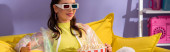 smiling young woman posing as doll with popcorn in 3d glasses on yellow couch, banner