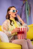 surprised young woman posing as doll with popcorn in 3d glasses on yellow couch
