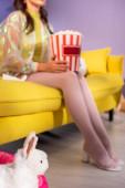 Spielzeugkaninchen und verschwommene junge Frau posieren als Puppe mit Popcorn auf gelbem Sofa