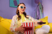 young woman posing as doll with popcorn and remote control in 3d glasses on yellow couch