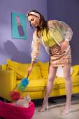 junge Frau posiert als Puppe mit Staubwedel in der Nähe von Spielzeughase zu Hause