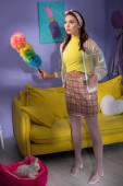junge Frau posiert zu Hause als Puppe mit Staubwedel