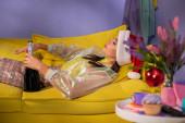 mladá žena v Santa klobouku vydávající se za panenku na žluté pohovce se šampaňským
