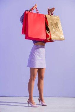 Bebek gibi giyinmiş, menekşe renkli arka planda kırmızı alışveriş torbaları olan genç bir kadın.