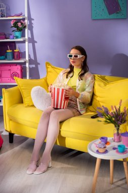 Young woman posing as doll with popcorn in 3d glasses on yellow couch stock vector
