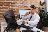 Businessman pointing at computer while talking on smartphone near coffee to go on blurred foreground