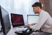 üzletember számítógépet használ pénzügyi piaci grafikonokkal monitorokon telefon közelében elmosódott előtérben