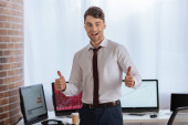 Cheerful businessman showing like gesture with computers on blurred background