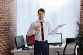 Mosolygó üzletember mutató kéz és ujj közelében számítógépek elmosódott háttér
