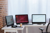 Computers with charts of finance stocks on monitors, coffee to go and telephone in office