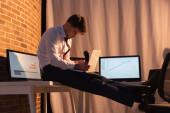 üzletember kezében digitális táblagép és telefon készülék közelében számítógépek este