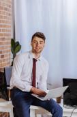 Veselý podnikatel pomocí notebooku v blízkosti odnést kávu a počítače v kanceláři