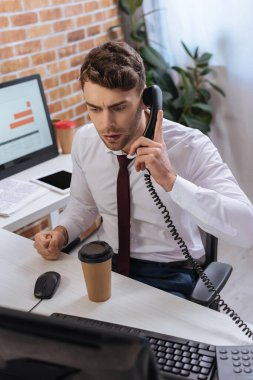 Businessman talking on telephone near coffee to go and computer on blurred foreground stock vector