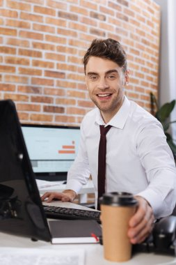 Smiling businessman taking coffee to go near computer on blurred foreground stock vector