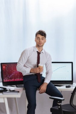 Young businessman holding coffee to go near computers with finance charts on blurred background stock vector