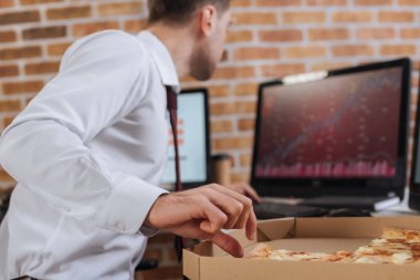 Businessman taking tasty pizza in box near computers on blurred background in office stock vector