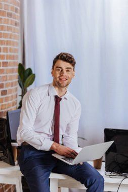 Cheerful businessman using laptop near takeaway coffee and computers in office stock vector