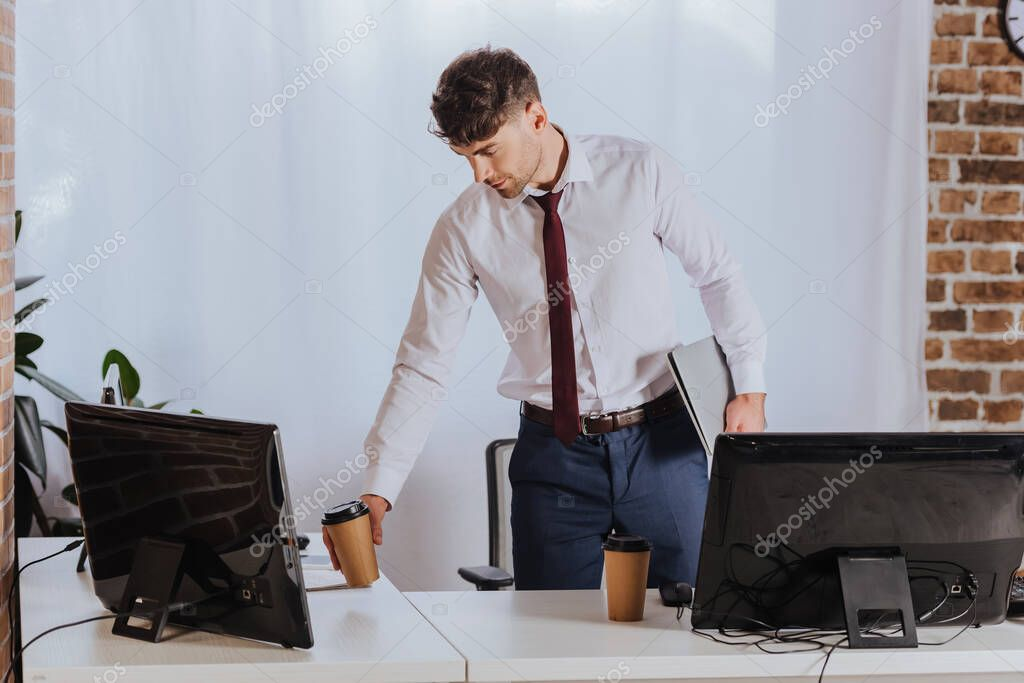 Young businessman taking coffee to go while holding laptop near computers in office stock vector
