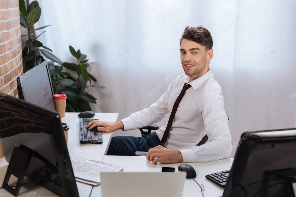 Smiling businessman looking at camera near computers, takeaway coffee and newspaper on blurred foreground stock vector