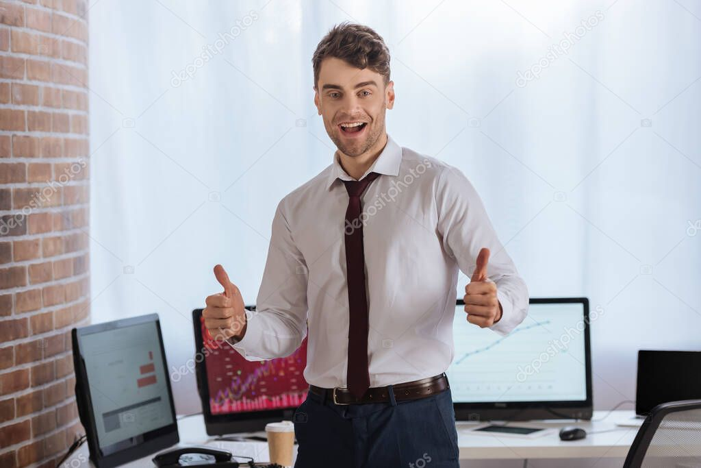 Cheerful businessman showing like gesture with computers on blurred background stock vector