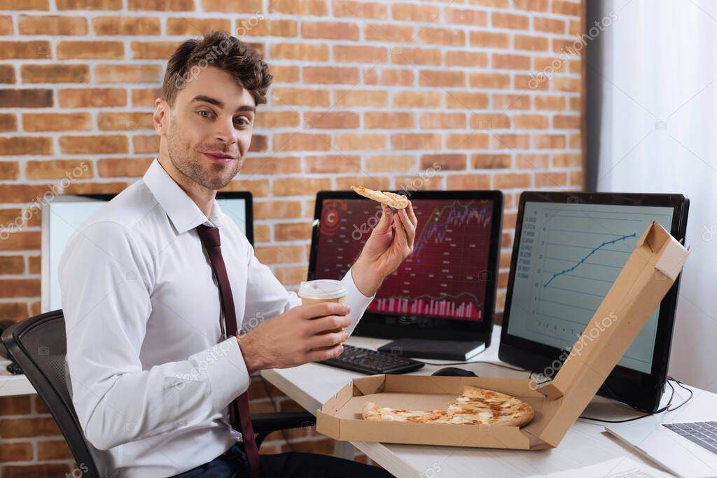 Smiling businessman holding pizza and takeaway coffee near computers on blurred background stock vector