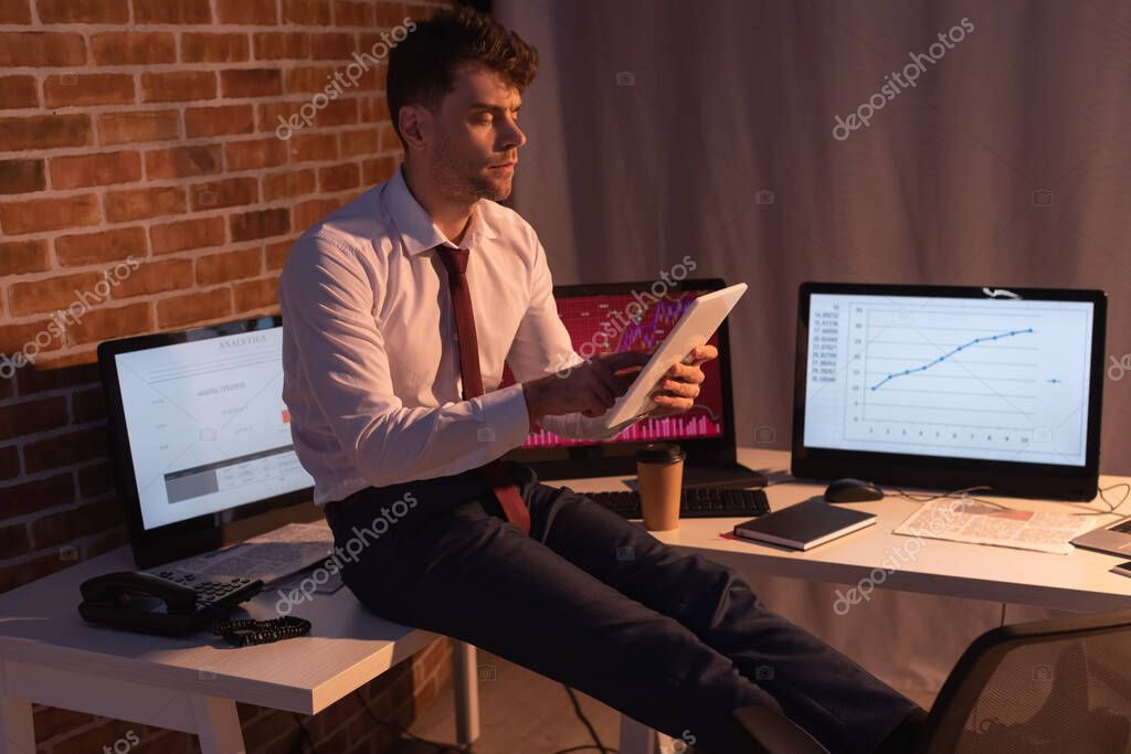 Businessman using digital tablet near computers, telephone and newspaper on blurred background in evening stock vector