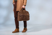 partial view of stylish man holding leather briefcase and standing with hand in pocket on grey