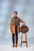 Stilvoller Mann in Wintermantel und Brille steht neben Holzstuhl und hält Aktentasche auf grau