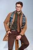 stylischer Mann in Wintermantel und Brille auf Holzstuhl sitzend mit Hand in Tasche auf grau