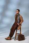 volle Länge der trendige Mann in Wintermantel und Brille sitzt auf Holzstuhl mit den Händen in Taschen in der Nähe Aktentasche auf grau