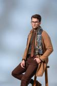 stylischer Mann im Winteroutfit und Brille auf Holzstuhl sitzend mit der Hand in der Tasche auf grau