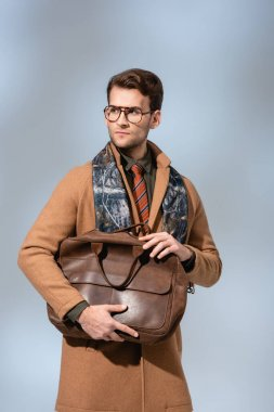Trendy man in winter coat holding brown briefcase on grey stock vector