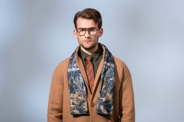 Stylish man in winter coat looking at camera on grey stock vector