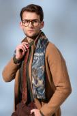 trendy man in winter coat and glasses adjusting tie on grey